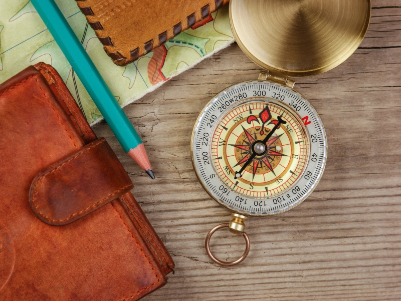compass wallet and passport on a wooden table